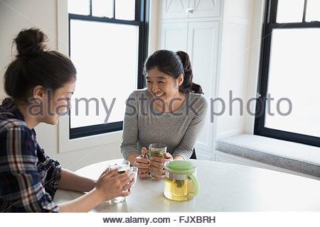 Mutter und Tochter im Teenageralter Tee trinken und reden - Stockfoto