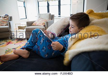 Junge im Pyjama mit digital-Tablette auf sofa - Stockfoto