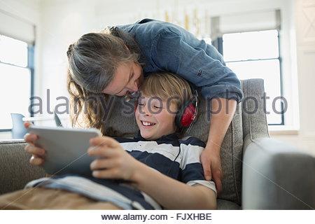 Mutter Sohn küssen mit Kopfhörer mit digital-Tablette - Stockfoto