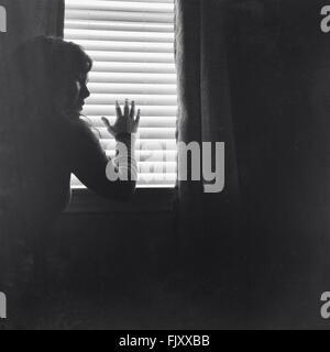 Junge Frau gegen Fenster zu Hause - Stockfoto