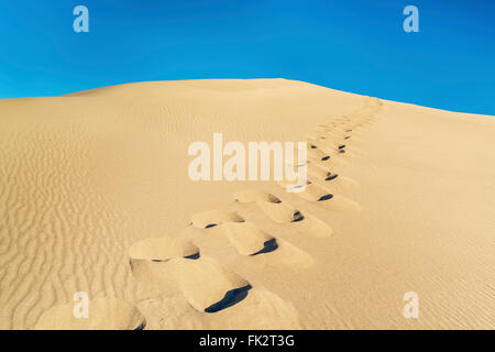 Mann: Spuren auf einer Sanddüne und blauer Himmel in Great Sand Dunes National Park, Colorado - Stockfoto