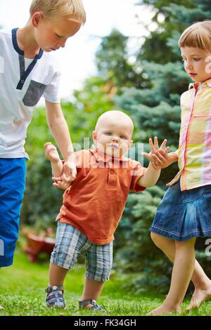 Zwei stolze Geschwister helfen Baby, erste Schritte in einem Garten zu lernen - Stockfoto