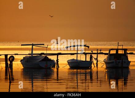 Drei kleine Fischerboote dock in Dalmatien bei Sonnenaufgang, Kroatien. - Stockfoto