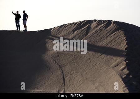 Zwei Männer in der Silhouette auf einer Sanddüne, Imperial Sand Dunes Recreation Area, Kalifornien USA - Stockfoto