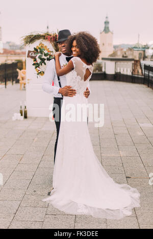 Afrikanische Hochzeitspaar glücklich in die Arme von einander auf dem Dach. Lemberg alte Architektur auf Hintergrund - Stockfoto