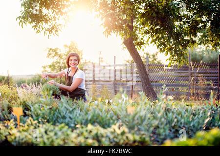 ein junges m dchen h lt eine keimling pflanze und ein spaziergang durch die g rten der farm mit. Black Bedroom Furniture Sets. Home Design Ideas