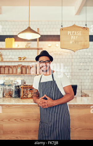 Coffee-Shop-Arbeiter lächelnd zu Kamera, an der Theke stehen. Glücklich Jüngling mit Schürze und Hut, Café Theke - Stockfoto