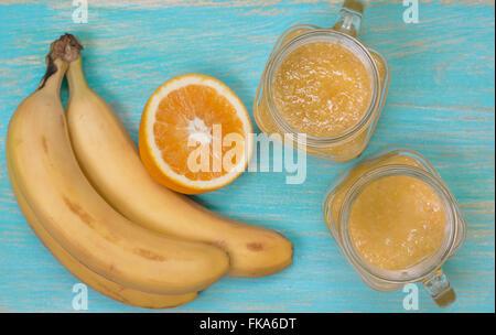 Smoothies mit Orangen und Bananen in einem Einmachglas auf einem blauen hölzernen Hintergrund (Draufsicht, selektiven - Stockfoto