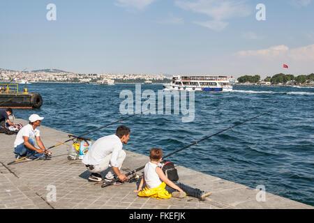 Männer Angeln am Kai und Personenfähre vorbei, den Bosporus, Istanbul, Türkei - Stockfoto