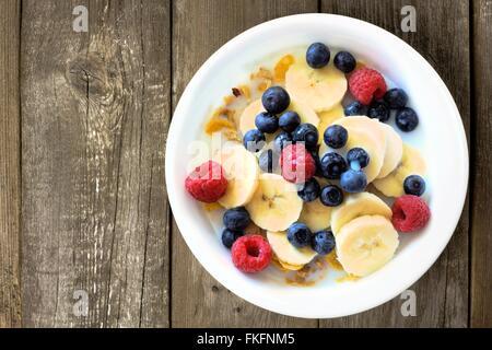 Frühstücks-Cerealien mit Blaubeeren, Bananen und Himbeeren auf einem rustikalen Holz Hintergrund, Draufsicht - Stockfoto