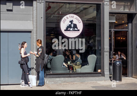 Zwei Frauen reden außen Joe & The Juice in Soho in New York City - Stockfoto