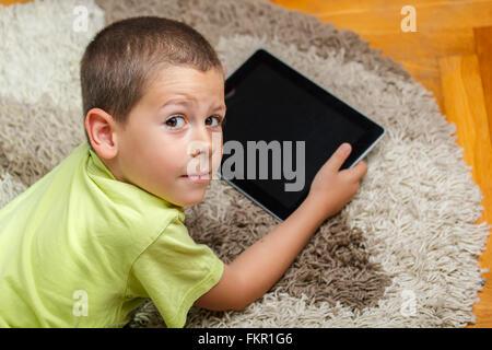Kleiner Junge am Boden liegend und mit digital-Tablette - Stockfoto