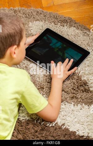 Junge am Boden liegend und mit digital-Tablette - Stockfoto