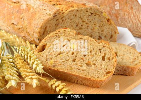 Nahaufnahme von geschnittenem Brot auf Holzbrett - Stockfoto