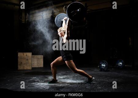 Seitenansicht der jungen Frau Gewichtheben Langhantel in dunklen Turnhalle Stockfoto
