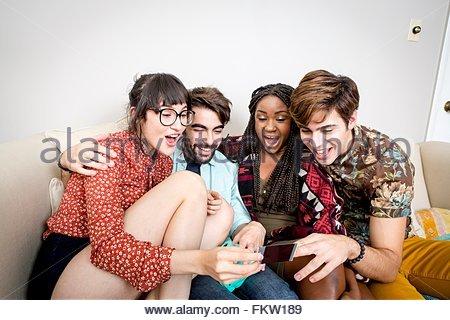 Zwei junge Hipster-Paare auf Wohnung Sofa lachen über sofortige Foto - Stockfoto