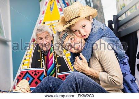 Porträt von älteres Paar und Enkel tragen Cowboyhut am Boden des Wohnzimmers - Stockfoto