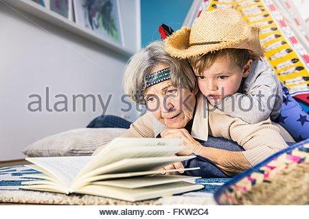 Ältere Frau liest Enkel tragen Cowboyhut am Boden des Wohnzimmers - Stockfoto