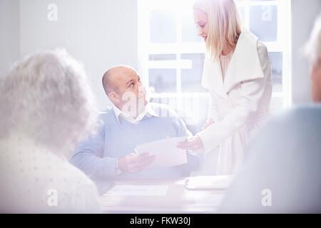 Sekretärin Übergabe Papierkram an Geschäftsmann im Büro - Stockfoto