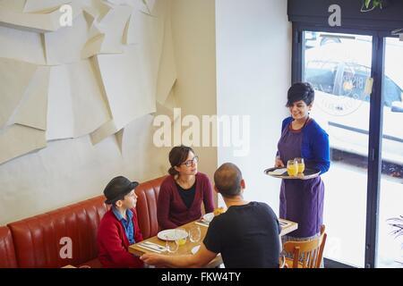 Kellnerin, die das Mittagessen im Restaurant Familie mit Sohn - Stockfoto