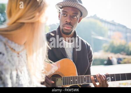 Paar im Park Gitarrespielen lernen - Stockfoto