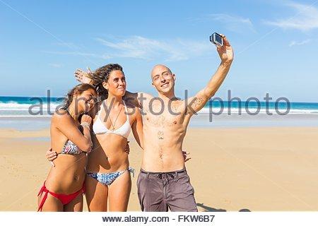 Mann und zwei junge Frauen tragen Badehosen unter Selfie am Strand, El Cotillo, Fuerteventura, Spanien - Stockfoto