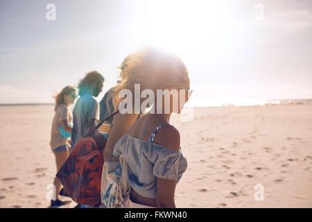 Aufnahme einer Gruppe von jungen Freunden an einem sonnigen Tag am Strand entlang spazieren. Männer und Frauen, die Sommer-Urlaub am Strand.