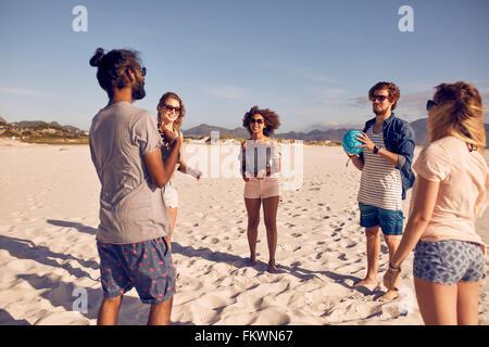 Gruppe von Jugendlichen stehen im Kreis am Strand und mit Ball spielen. Junge Freunde spielen Ball Spiel an einem Sandstrand.