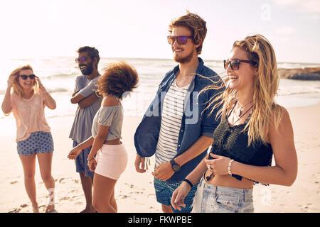 Gruppe von Freunden zu Fuß am Strand im Sommer. Glückliche junge Menschen genießen einen Tag am Strand.