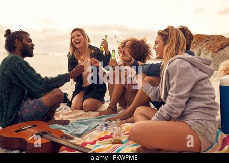 Glückliche Freunde Party am Strand mit Getränken und Wunderkerzen. Heterogene Gruppe von Freunden zusammen am Strand - Stockfoto