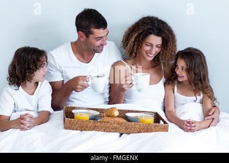 Glückliche Familie mit Frühstückstablett auf Bett sitzen - Stockfoto