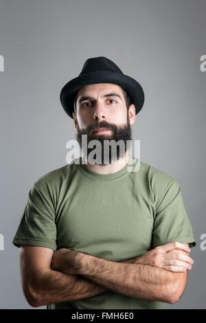 Ernsten zuversichtlich bärtigen Mann mit verschränkten Armen Blick in die Kamera. Kopfschuss-Porträt über graue - Stockfoto