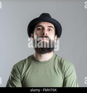 Ernst hart bärtiger macho Mann Blick in die Kamera. Kopfschuss Nahaufnahme Portrait über graue Studio-Hintergrund. - Stockfoto