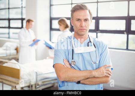 Porträt des Arztes Stand mit verschränkten Armen - Stockfoto