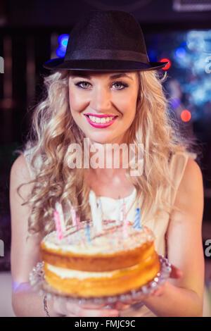 Lächelnde Frau hält einen Kuchen - Stockfoto