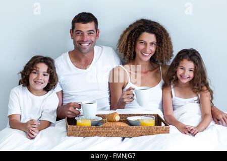 Porträt einer Familie mit Frühstückstablett im Bett sitzend - Stockfoto