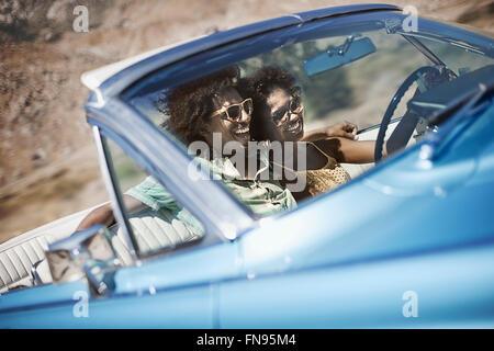 Ein junges Paar, Mann und Frau in einem blassen Blau Cabrio auf offener Straße - Stockfoto