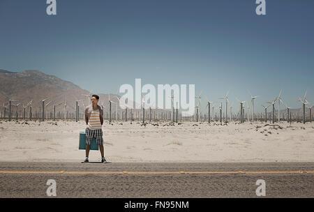 Ein Mann mit einem Koffer auf der Seite eine Autobahn mit Windkraftanlagen im Hintergrund. - Stockfoto