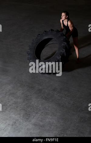 Frau heben Traktorreifen in Turnhalle - Stockfoto