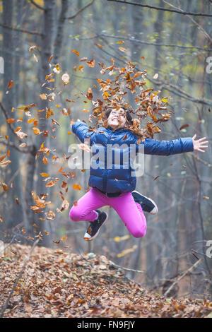 Mädchen, springen und werfen im Herbst Blätter in der Luft - Stockfoto