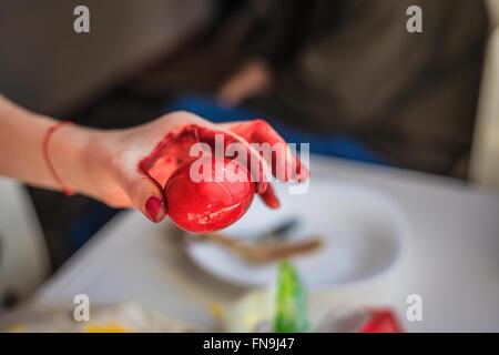 Frau malt ein rotes Osterei - Stockfoto