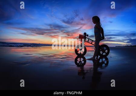 Schwarze Silhouette von Kleinkind - run Bike-Fahrer stehen an nassen Sand Strand, Blick auf Meer Surfen und farbenfrohen Sonnenuntergang Himmel.