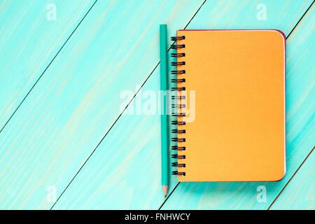 Leere Spiral-Notizbuch mit Bleistift auf dem hölzernen Hintergrund. Ansicht von oben. - Stockfoto