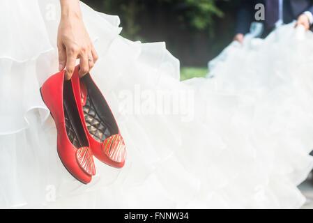 Braut hält rote Schuhe und Bräutigam halten den Rock - Stockfoto