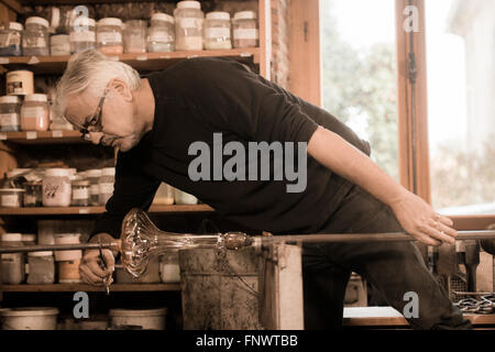 Glasbläser bilden geschmolzenes Glas in seiner Werkstatt - Stockfoto