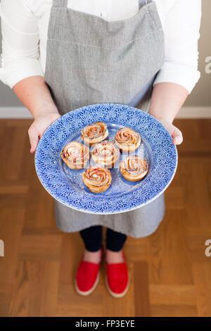 Frau zeigt sich ihre hausgemachten Brötchen auf einem blauen Teller - Stockfoto