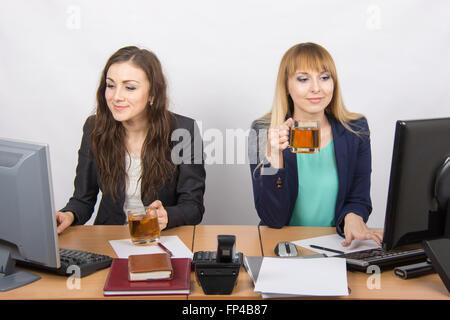 Zwei schöne junge Mädchen trinken Tee, Büro hinter einem Schreibtisch und arbeiten auf dem computer - Stockfoto