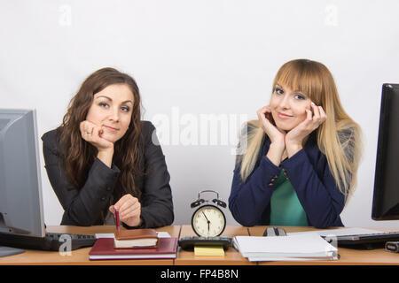 Zwei Büroangestellte geprüft gegen die Uhr am Ende des Arbeitstages - Stockfoto
