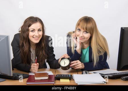 Zwei glückliche Büroangestellte geprüft gegen die Uhr am Ende des Arbeitstages - Stockfoto