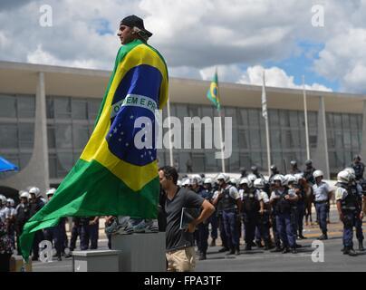 Ein Anti-Regierungs-Demonstranten trägt eine brasilianische Flagge, wie er Tausende vor dem Präsidentenpalast Planalto - Stockfoto